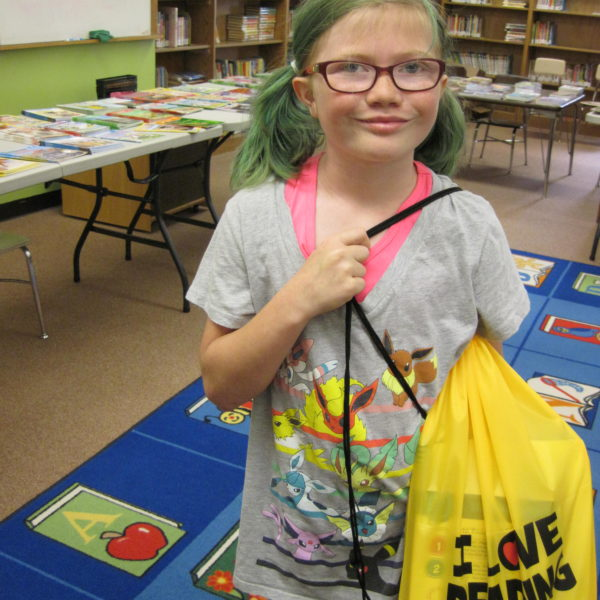 Second grade girl holding back pack full of books