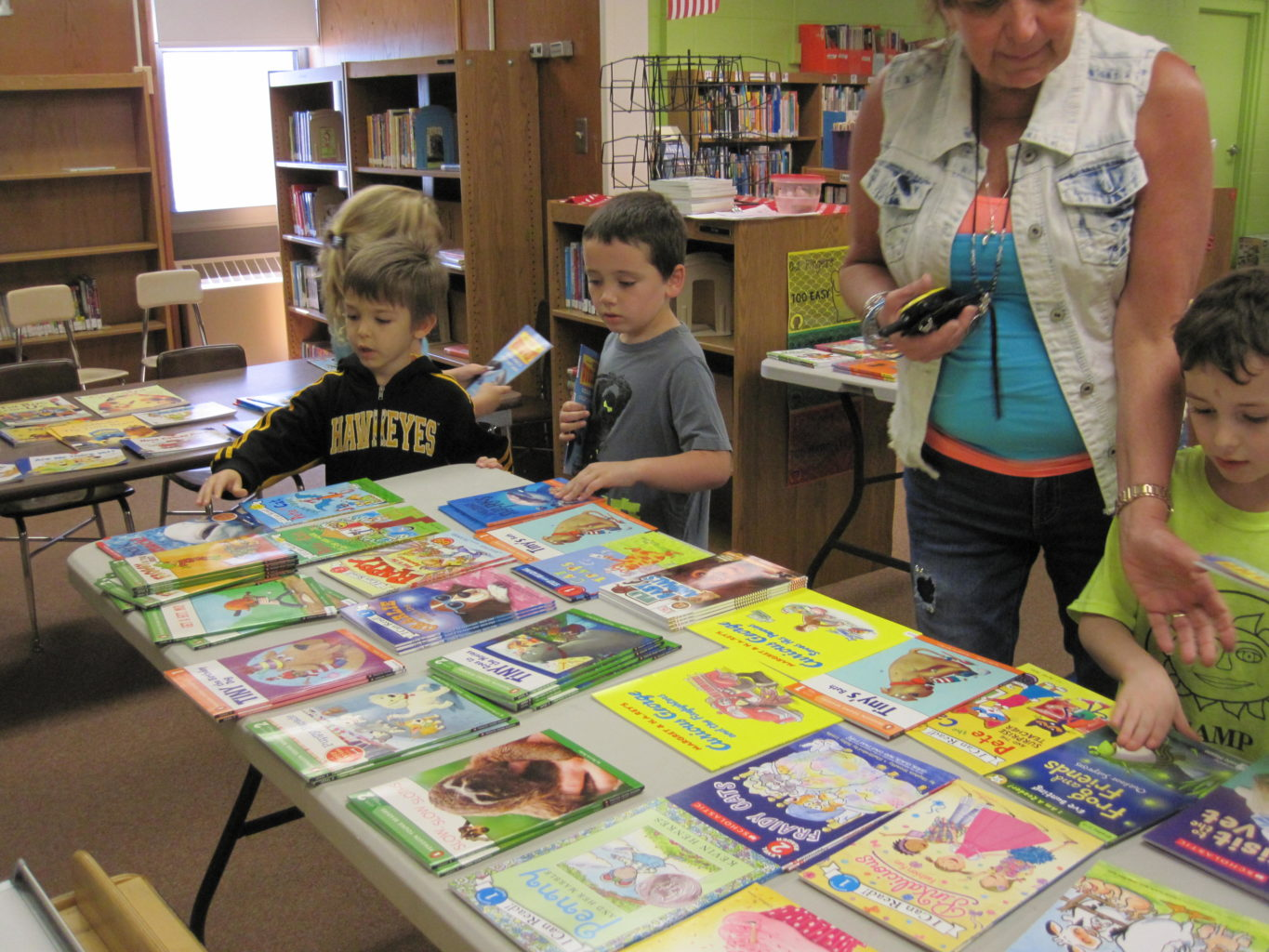 Boys looking at table of books